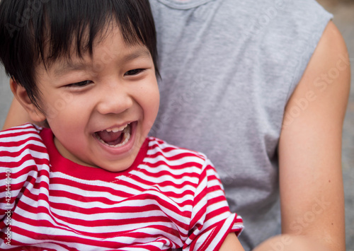 Fototapeta Asian cute child boy laughing with mouth open wide, seeing whitening teeth in hag father