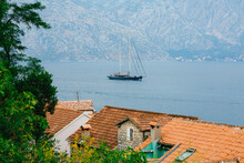 Sailboat Floats On The Sea Through The Branches Over The Roofs Of The Houses Against The Background Of Mountains