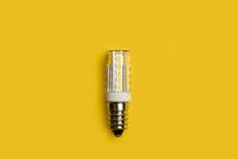 Bombilla De Luz Led Sobre Un Fondo Amarillo Liso Y Aislado. Vista Superior Y De Cerca. Copy Space