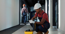 Portrait Of African Young Technician Worker Searching Tools Inside Instrument Case Repairing Lighting Electric System In Modern Apartment Building Posing For Camera.