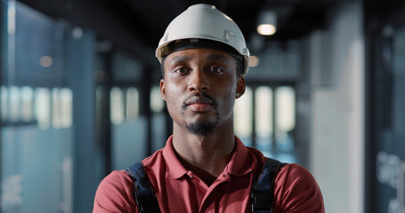 African young engineer worker electricity specialist wearing hardhat and uniform using tablet computer for managing lighting electric system inside office.