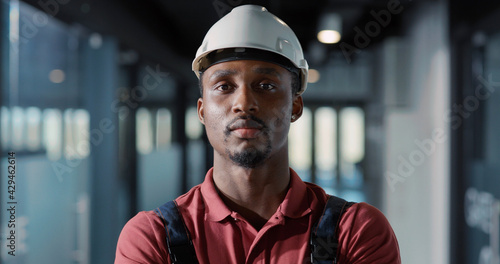 African young engineer worker electricity specialist wearing hardhat and uniform using tablet computer for managing lighting electric system inside office. - fototapety na wymiar