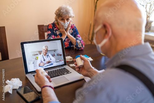 Obraz Senior couple consulting with a doctor on laptop at home  - fototapety do salonu