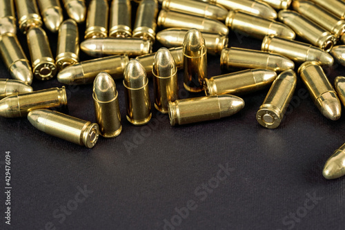 Foto Many brass gun bullets on black table closeup view, space for text bottom part