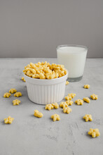 Honey Stars Breakfast Cereal In White Bowl And Glass Of Milk On Background. Healthy Whole Grain Food. Kid's Meal.