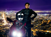 Sporty Female Motorcyclist Or Biker Wearing A Leather Jacket And Helmet On A Road At Night With A Motorcycle Above A Scenic View Of The San Francisco Cityscape