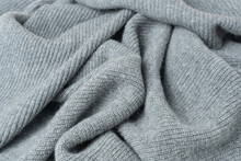Background Of Gray Woolen Knitted Fabric Lying In Folds.