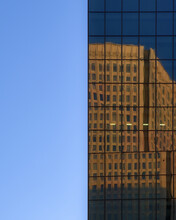 Split Perspective Of A Clear Blue Sky And The Mirrored Glass Exterior Of A Modern Skyscraper Reflecting Another Nearby Building