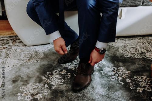 Fototapeta Closeup shot of a groom lacing shoes