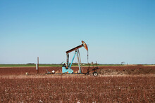 Rusty Blue Pumpjack In A Harvested Cotton Field