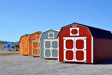 Colorful Wooden Sheds On Display. American Shed Is Typically A Simple, Single-story Roofed Structure In A Back Garden Or On An Allotment That Is Used For Storage, Hobbies, Or As A Workshop.