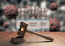 Judge Gavel Or Law Gavel On Wooden Table With Coronavirus Vaccine In The Background. Concept Of Justice And Crimes Trials Of The Covid-19 Pandemic.