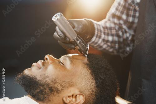 Young African-american man visiting barbershop - fototapety na wymiar