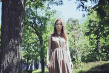 木々の小道で佇む美しい女性のポートレート