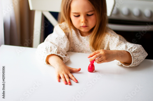 Fotografija Little girl paints her nails with pink nail polish