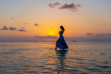 Young Beauty Girl Dancing At Tropical Beach On Sea Water At Paradise Island At Sunset. Summer Concept