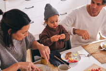 Crop Family With Little Daughter Having Breakfast At Home