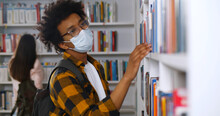 Young African-american Man Wearing Mask Looking For Book In Library