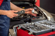 Male hands with wrench and car part