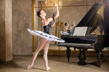 Young Ballerina In A White Tutu Dancing On Beautiful Old Piano In A Vintage Interior