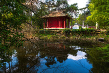 Indochinese Temple Of Remembrance. Red Temple Over The Pond With Beautiful Reflection In Tropical Garden Of Paris In Vincennes Forest. Paris, France.