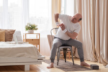 Senior Caucasian Man Stretching Side Sitting On Chair At His Living Room.
