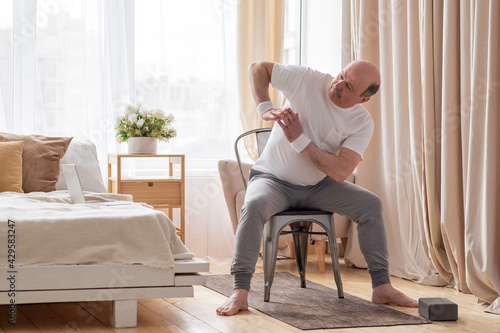 Canvas Senior caucasian man stretching side sitting on chair at his living room