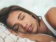 Portrait of young beautiful  female in white lingerie. Sexy carefree woman lies on bed in posh apartment or hotel room. She wakes up. She sleeping at sunny lazy morning. Closed eyes