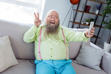 Portrait Of Positive Cheerful Guy Sit On Sofa Take Selfie Fingers Show V-sign Beaming Smile Free Time Indoors