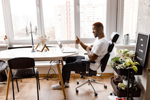 Happy African American Businessman Is Sitting At The Desk, Using Laptop, Working From Home Office. Successful Male Freelancer Having A Video Meeting With Colleagues, Agree With Them, Showing Thumbs Up