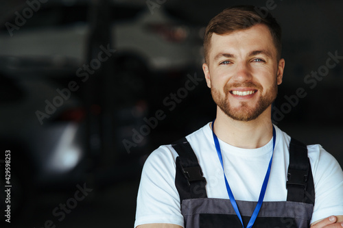 Fotografia Auto mechanic standing in his workshop in front of a car