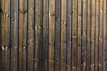 Texture Of Barn Wall Made From Homemade Rough Sawn Timber. Knotty Boards Treated With Varnish And Pine Tar.