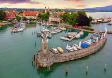 Lindau, Germany. Antique Bavarian Town At Lake Constance (Bodensee). Monument With Statue Of Lion At Entrance To Port, Yachts By Piers. Summer Landscape Blue Sky.