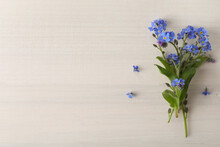 Beautiful Blue Forget-me-not Flowers On White Wooden Table, Top View. Space For Text