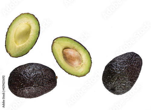 Halved avocado with a stone and two whole ripe avocados cutout on a white backgr Fototapet
