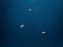 Aerial View Of Three Boats Moored Offshore And Surrounded By A Deep Blue Sea In Caminia, Calabria, Italy.