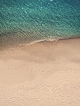 Aerial View Of A Deserted Beach And Calm Sea With Footprints On The Shore At Early Morning In Sant'Andrea Apostolo Dello Ionio, Calabria, Italy.