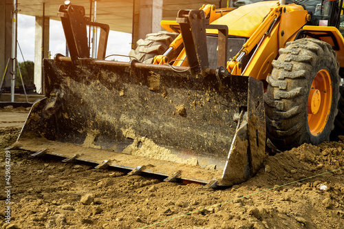 Canvas Print The bulldozer moves and spreads the soil and rubble on the embankment of the road