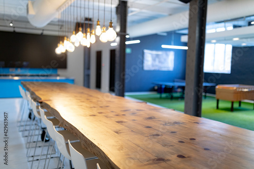 Modern empty office conference room with long table industrial light bulbs and screen