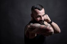 Uomo Moro Muscoloso, Tatuato Con La Barba, Stai Un Posizione Di Combattimento Pronto All'attacco , Isolato Su Sfondo Nero