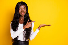 Photo Portrait Of Girl With Long Hair Curious Pointing Holding On Hand Empty Space Isolated Vivid Yellow Color Background