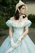 A Beautiful Young Woman In A Historical Blue Dress With An Umbrella, Gloves And A Hat. Dress On A Woman Of The 19th Century. Design For The Book Cover