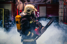 Portrait Of Young Fireman Standing And Holding A Chainsaw In The Middle Of The Chainsaw's Smoke  .
