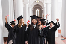 Asian Graduate With Diploma Showing Yes Gesture Near Excited Friends
