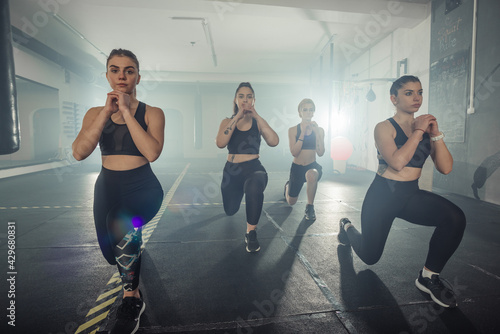 Valokuvatapetti Group of sportswomen in sportswear doing lunge exercise at the gym with their le
