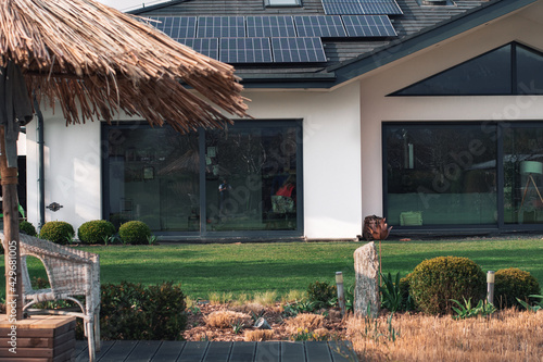 Nowoczesny dom z dużymi oknami.  Zielony trawnik  wizytówka pięknego domu, duży zielony ogród  z bambusowym parasolem w stylu boho - fototapety na wymiar