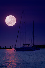 This Beautiful Pink Super Moonrise Above The Horizon Over Sailboats And Harbor Is A Perfect Night Time Illustration Of This Event.