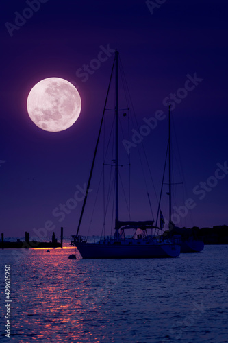 This beautiful pink Super Moonrise above the horizon over sailboats and harbor is a perfect night time illustration of this event. - fototapety na wymiar