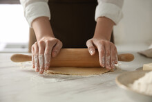 Woman Rolling Dough At Table In Kitchen, Closeup