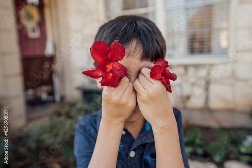 Boy holding red flowers in front of eyes фототапет